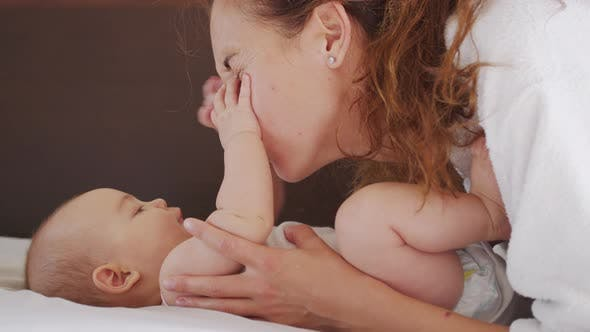 Authentic Close Up Shot of Young Mother Is Playing with Her Newborn Baby in a Nursery in a Morning