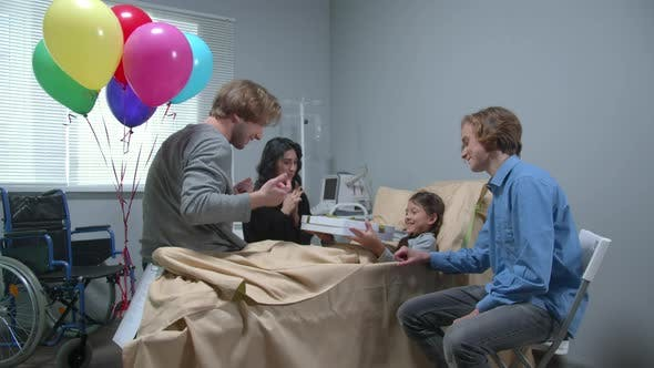 Thumbnail for Side View, Relatives Give a Present To Girl Who Lie on the Bed in the Hospital