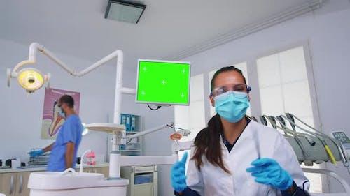 Patient Pov of Dentist Explaining Problem Using Greenscreen Monitor