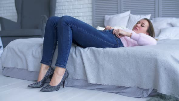 Thumbnail for Pretty Woman Struggling To Close Her Jeans on Bed