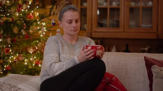 Thumbnail for Woman Relaxing on a Sofa Holding Mug and Drink Hot Tea at Christmas Evening