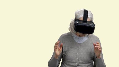 Mature Woman Wearing Virtual Reality Goggles.
