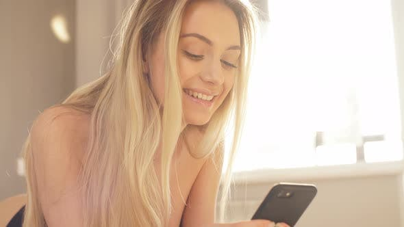 Thumbnail for Attractive Caucasian Woman Lying on Bed. Pretty Girl Using Phone and Resting.