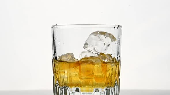 Thumbnail for Ice cubes fall in glass of whiskey over white