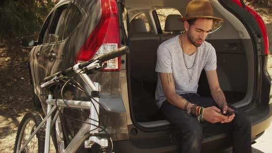 Thumbnail for hispanic man sitting in car using smartphone