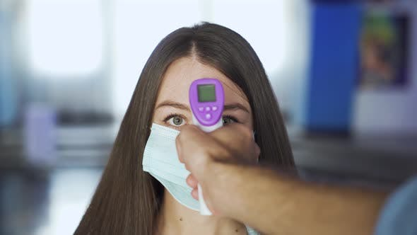 Woman in mask is checked for temperature in a mall