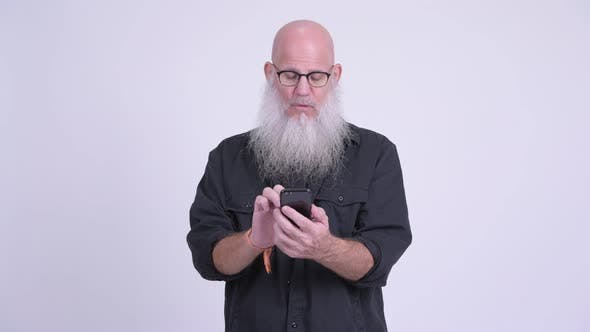 Thumbnail for Happy Mature Bald Bearded Man Using Phone and Getting Good News