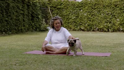 Asian Elderly woman play with dogs in the garden.