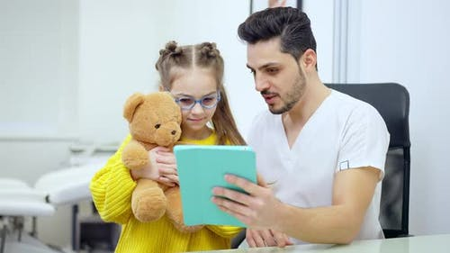 Pretty Girl Holding Teddy Bear As Positive Pediatrician Showing Tablet and Talking