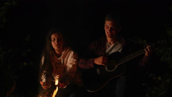 Thumbnail for Sitting by a campfire, roasting marshmallows and playing guitar