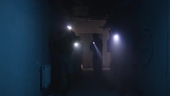 Soldiers with Flashlights Inspecting Dark Corridor