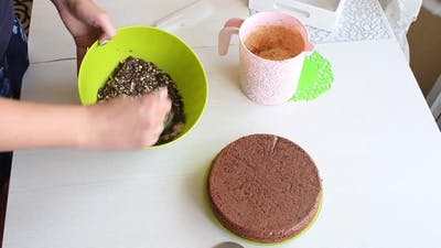 A Woman Mixes Peanuts And Chocolate In A Container.