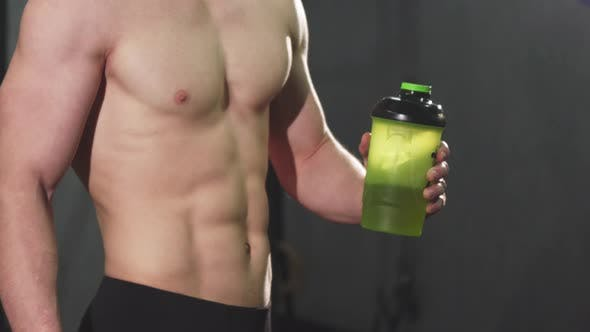 Thumbnail for Cropped Shot of a Shirtless Man with Perfect Abs Holding Water Showing Thumbs Up
