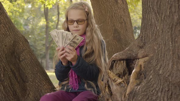 Thumbnail for Junge blond kaukasische Mädchen in photochromen Gläsern Zählen Geld und Denken Als Sitzen auf der