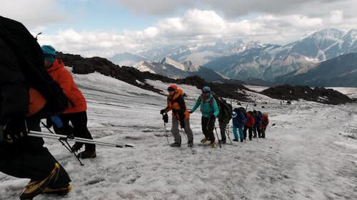 Travelers rise along the mountain pass on the ice slope