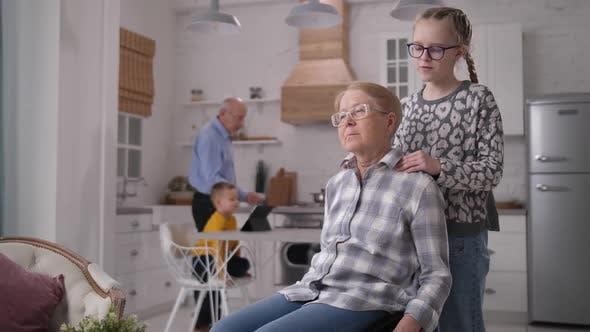 Caring Granddaughter Making Massage To Grandmother