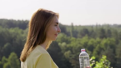 Woman Drinking Water From Bottle on Hot Sunny Summer Day
