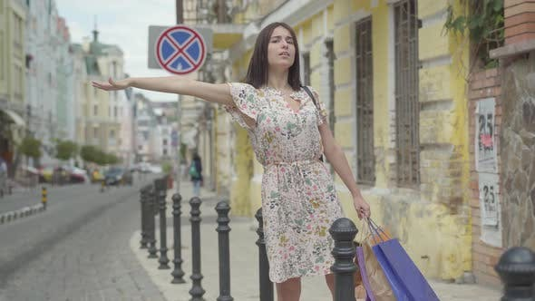 Cover Image for Carefree Beautiful Young Woman Wearing Summer Dress with Shopping Bags in Hands Trying To Catch a Taxi