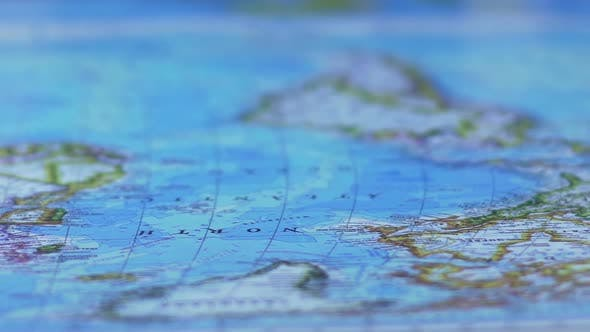 Thumbnail for World map poster laid out across table, toy car crossing it, travel by auto