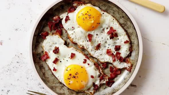Thumbnail for Two Fresh Fried Eggs with Crunchy Crisp Bacon Served on Rustic Plate