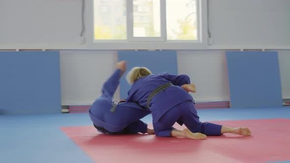 Female and Male Fighters in Kimonos Training for Jiu-Jitsu