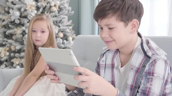 Side View of Happy Caucasian Boy Sitting with Tablet and Smiling, Pretty Girl Looking at Him at the