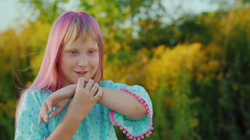 Cool Girl with Pink Hair Is Talking Through a Smart Watch