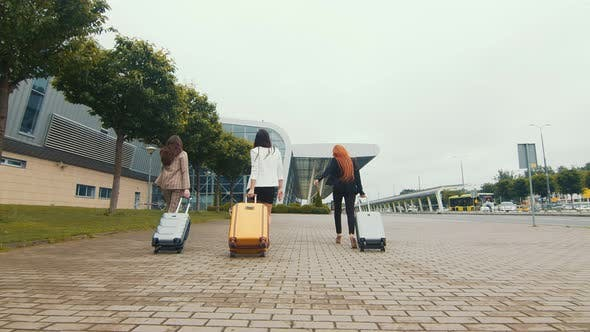 Thumbnail for Three Young Happy Girls Go on a Journey. Women Walk with Luggage in Hand To the Airport.