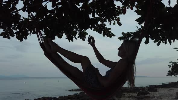 Thumbnail for A Woman in a Hammock on the Beach with a Phone.