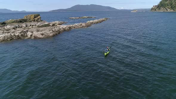 Thumbnail for Drone Rotating By Man Kayaking Through Rocks On Pacific Ocean Coastline