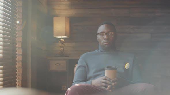 Thumbnail for Porträt eines afroamerikanischen Mannes, der mit Kaffeetasse sitzt