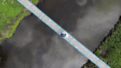 Aerial View on Top Newlyweds Bride and Groom Dance a Dance on the Bridge Over the River. The View