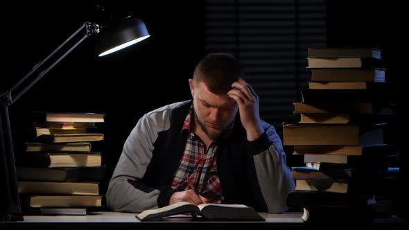 Thumbnail for Guy in the Light of the Lamp He Reads Terribly Headache. Black Background