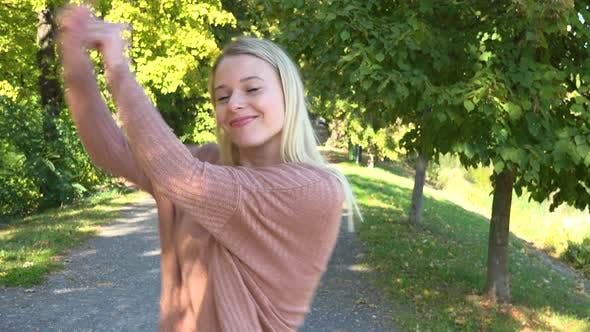 Thumbnail for A Young Beautiful Woman Dances in a Park on a Sunny Day - Closeup