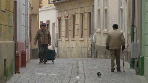 Old men walking on a narrow street