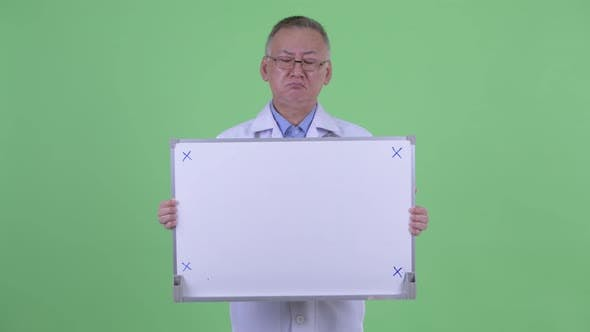 Thumbnail for Stressed Mature Japanese Man Doctor Holding White Board