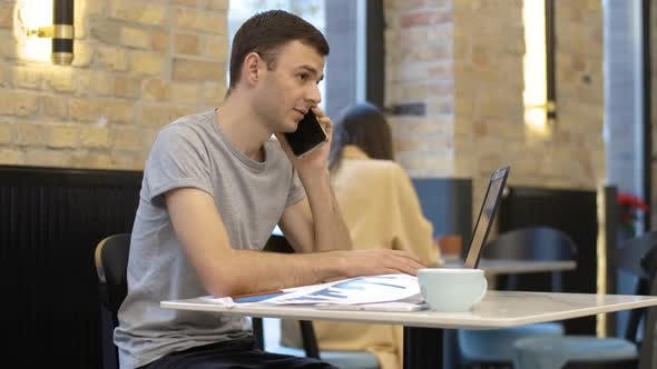 Thumbnail for Young Millennial Successful Businessman Talking on the Phone and Typing on Laptop Keyboard