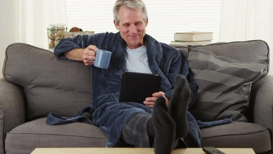 Thumbnail for Senior smiling reading tablet book on couch with coffee