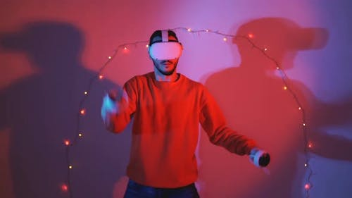 Young Man Fighting in Virtual Reality Using Swrods with Christmas Lights in the Background