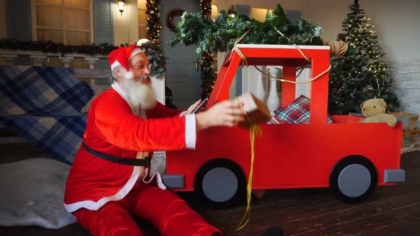 Thumbnail for Cheerful Father Christmas Preparing Gift with Tablet.
