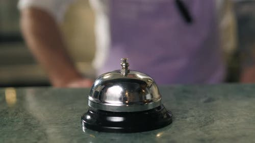 Close Up Macro Hand Chef and Ringing Bell Service on the Wooden in Kitchen Restaurant