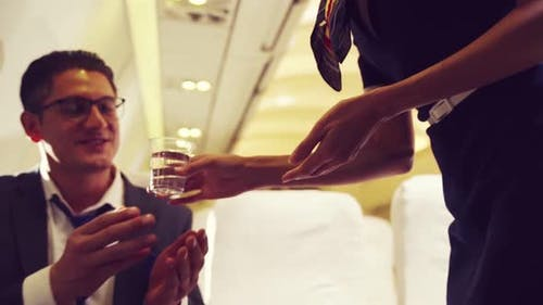 Cabin Crew Serve Water to Passenger in Airplane