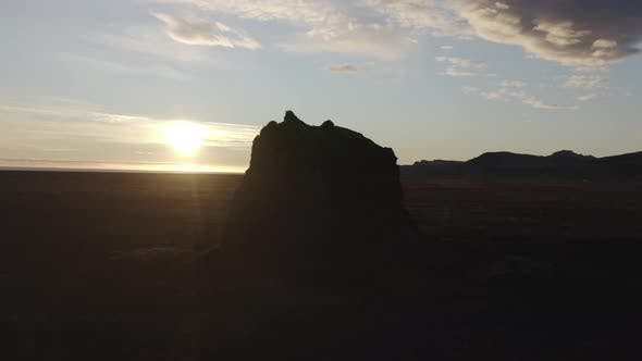 Rocks In Sparse Landscape As Glowing Sun Sets