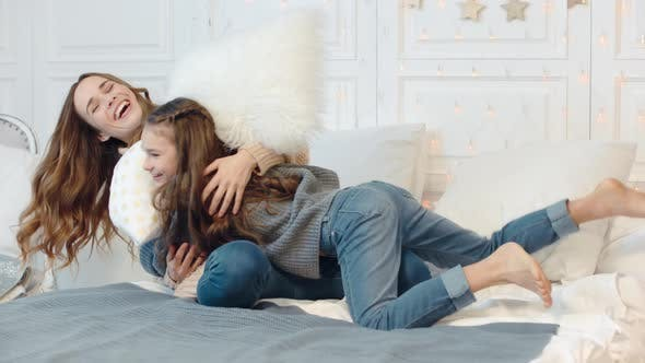 Thumbnail for Cheerful Ladies Fighting with Pillows on Bed in Luxury Apartment Together.