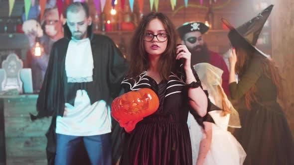 Junges attraktives Mädchen in Hexe Kostüm tanzt mit einem Jack-o-Laterne in Ihren Händen