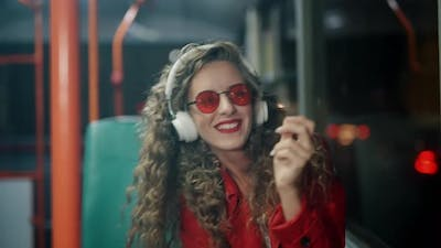 A Smiling Curly Woman in Headphones is Listening Music and Funny Dancing in Bus