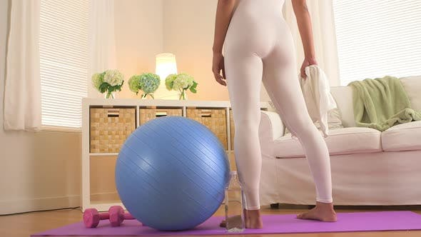 Thumbnail for Woman standing on yoga mat in living room