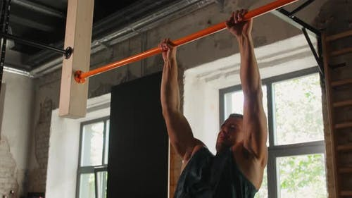 Young Man Exercising on Horizontal Bar in Gym