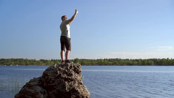 Thumbnail for A Young Man Stands on a Stone and Takes Pictures of Himself on the Phone. A Man Takes a Selfie in