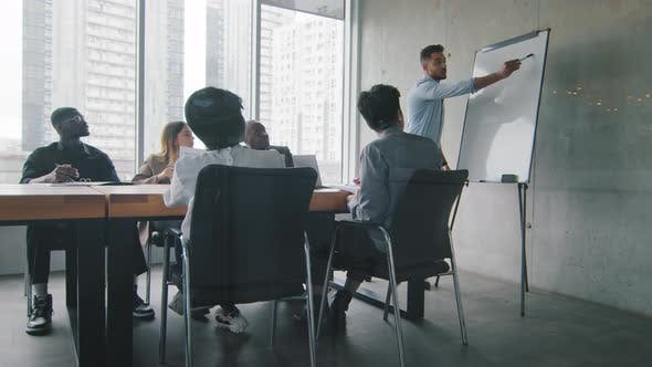 Hispanic Man Businessman Coach Gives Corporate Presentation for Diverse Multiracial Businesspeople